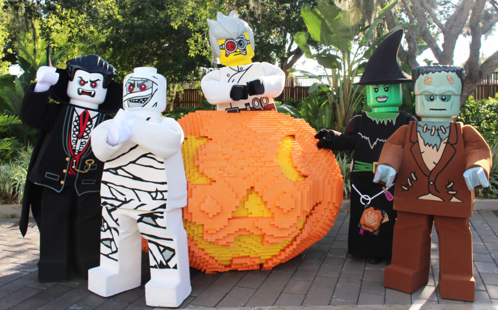 LEGOLAND characters in front of a Lego pumpkin.