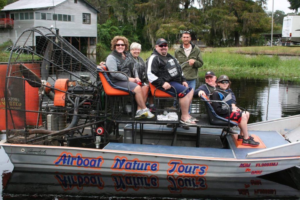 Group and airboat captain on boat before tour with Alligators Unlimited Airboat Tours