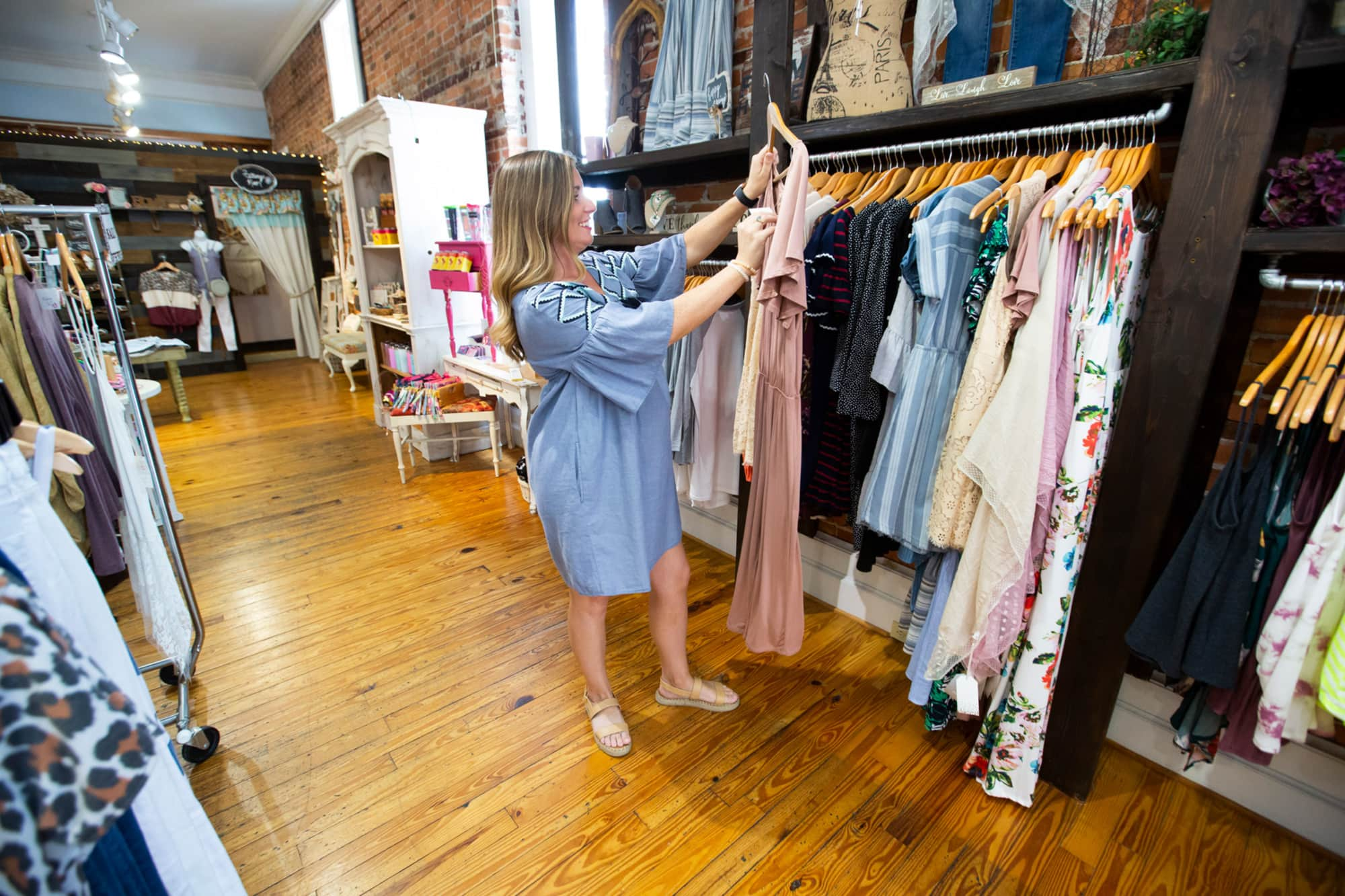 woman holding up a dress inside Amelia Paige Boutique in Lakeland, FL