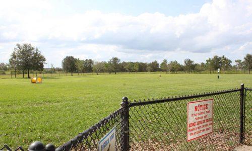 Entrance gate and field at Auburndale Dog Park at Lake Myrtle Park.