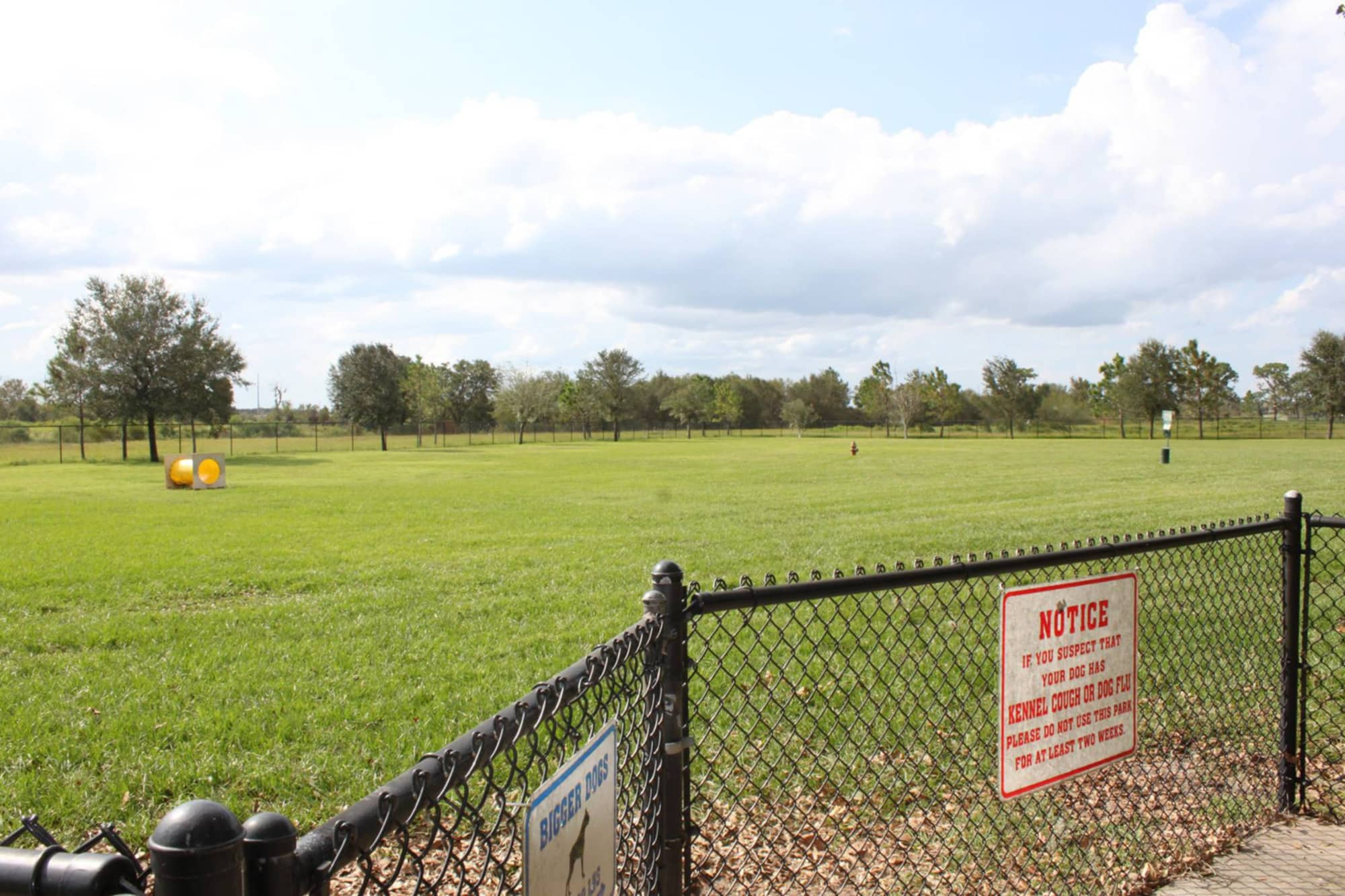 Entrance gate and field at Auburndale Dog Park at Lake Myrtle Park.