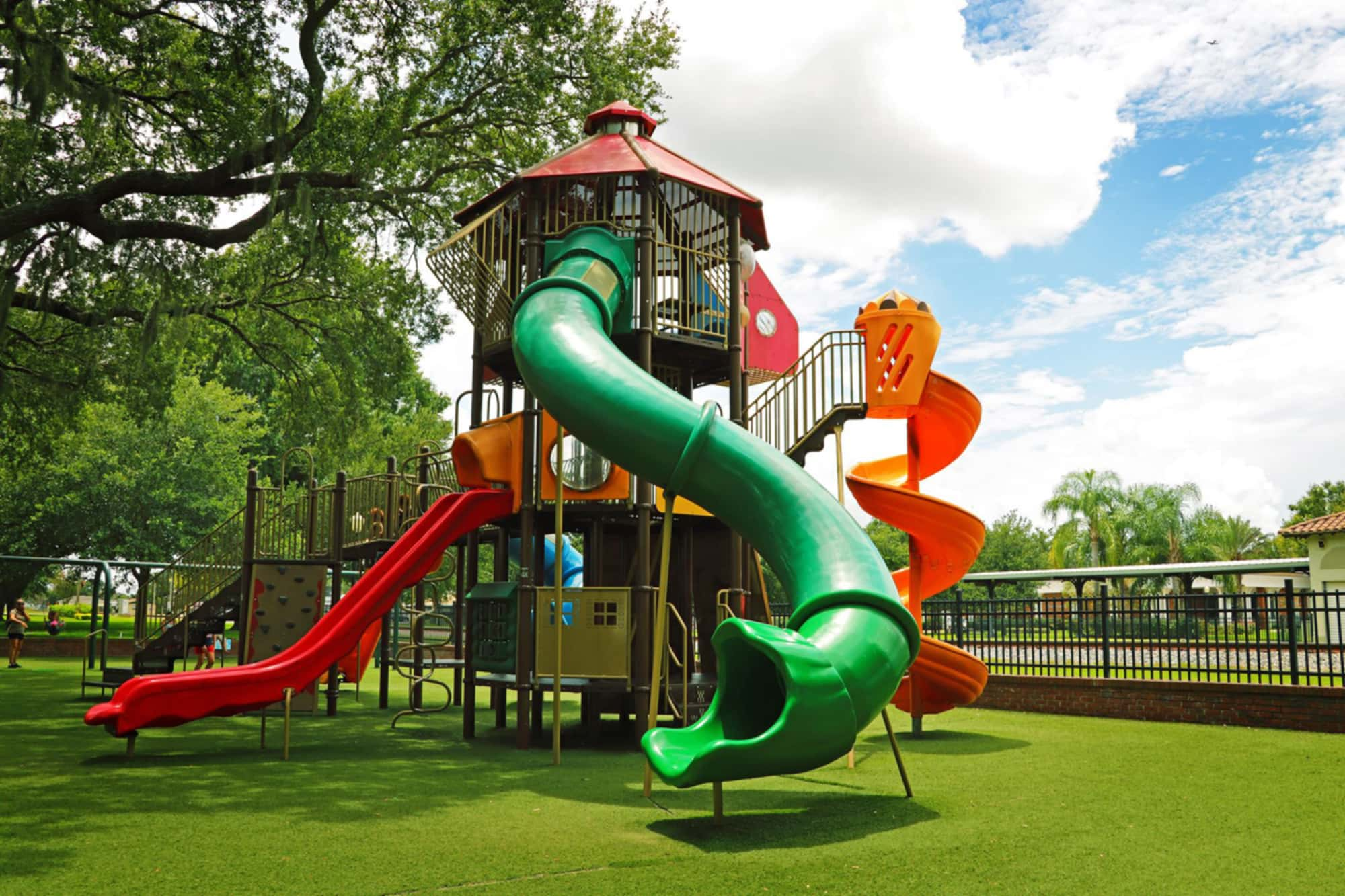 Playground equipment, including 3 slides and artificial grass at Downtown Auburndale, FL's City Park