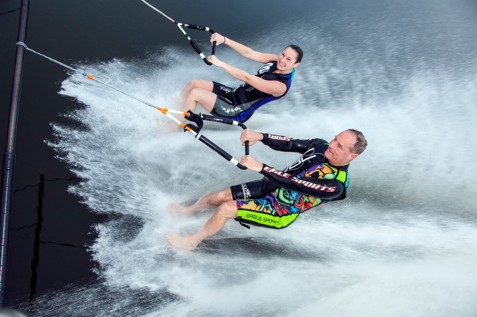 2 barefoot water skiers on water