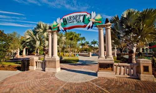 Entrance with trees and walkway to Barnett Family Park in Lakeland, FL