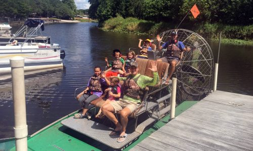 two families on airboat near river dock at Camp Mack in Lake Wales, FL