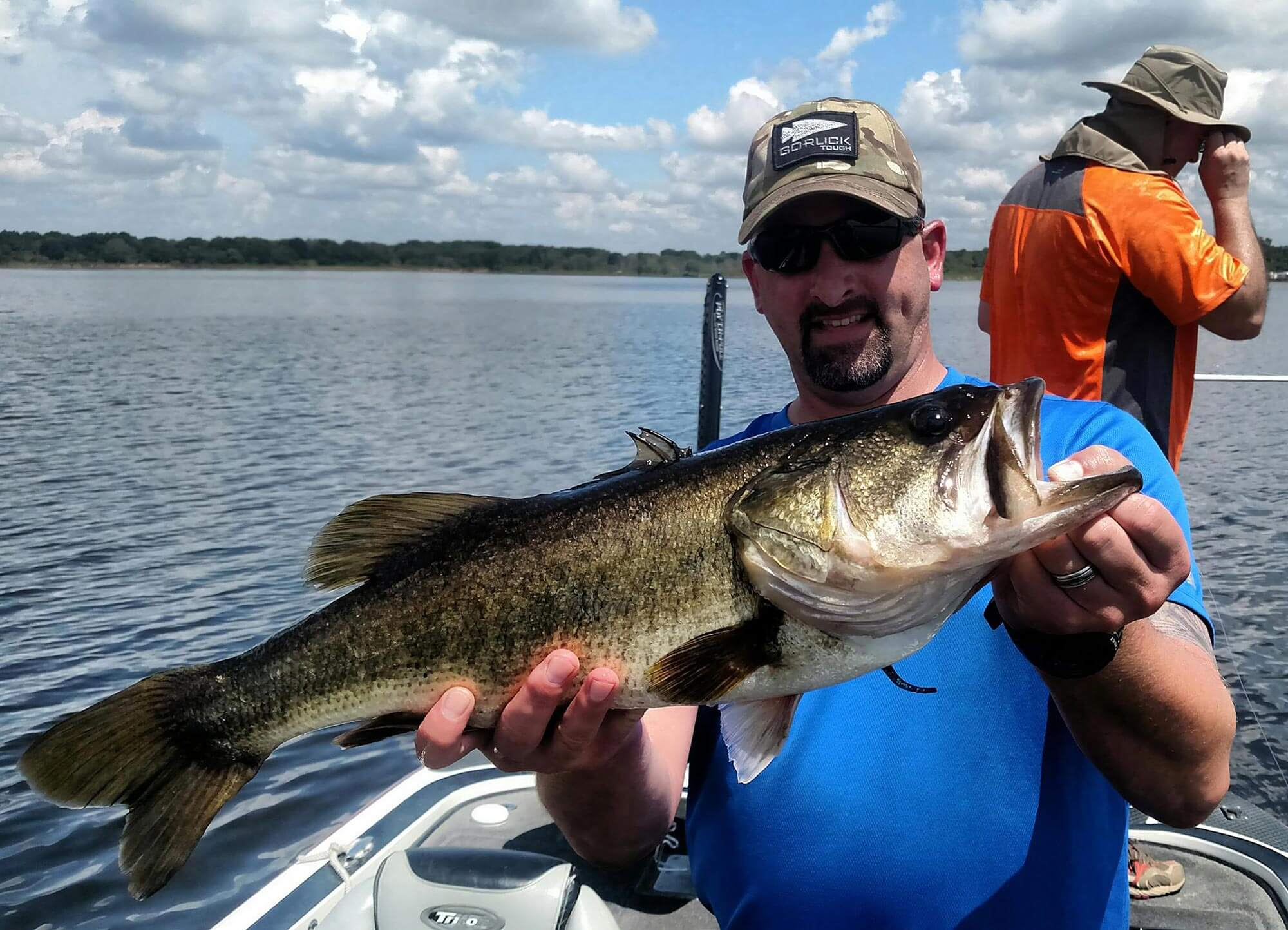 man holding large mouth bass while fishing with Central Florida Bucketmouths