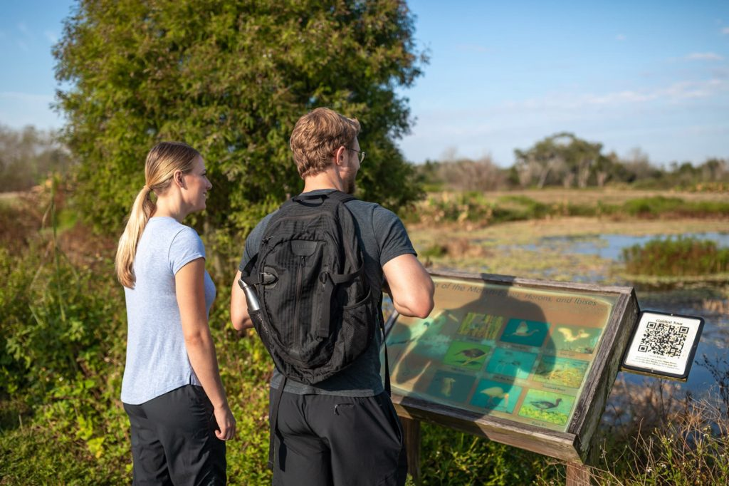 2 people reading trail sign overlooking lake at Circle B Bar Reserve in Lakeland, FL