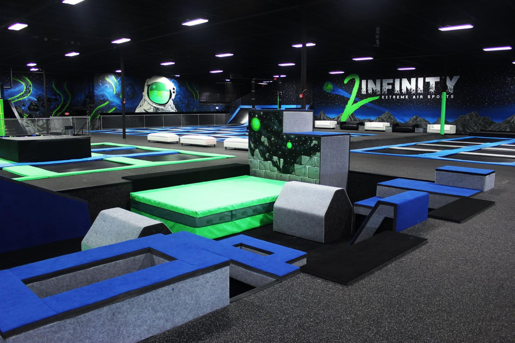 Open floor at DEFY Lakeland showing trampolines and agility boxes.