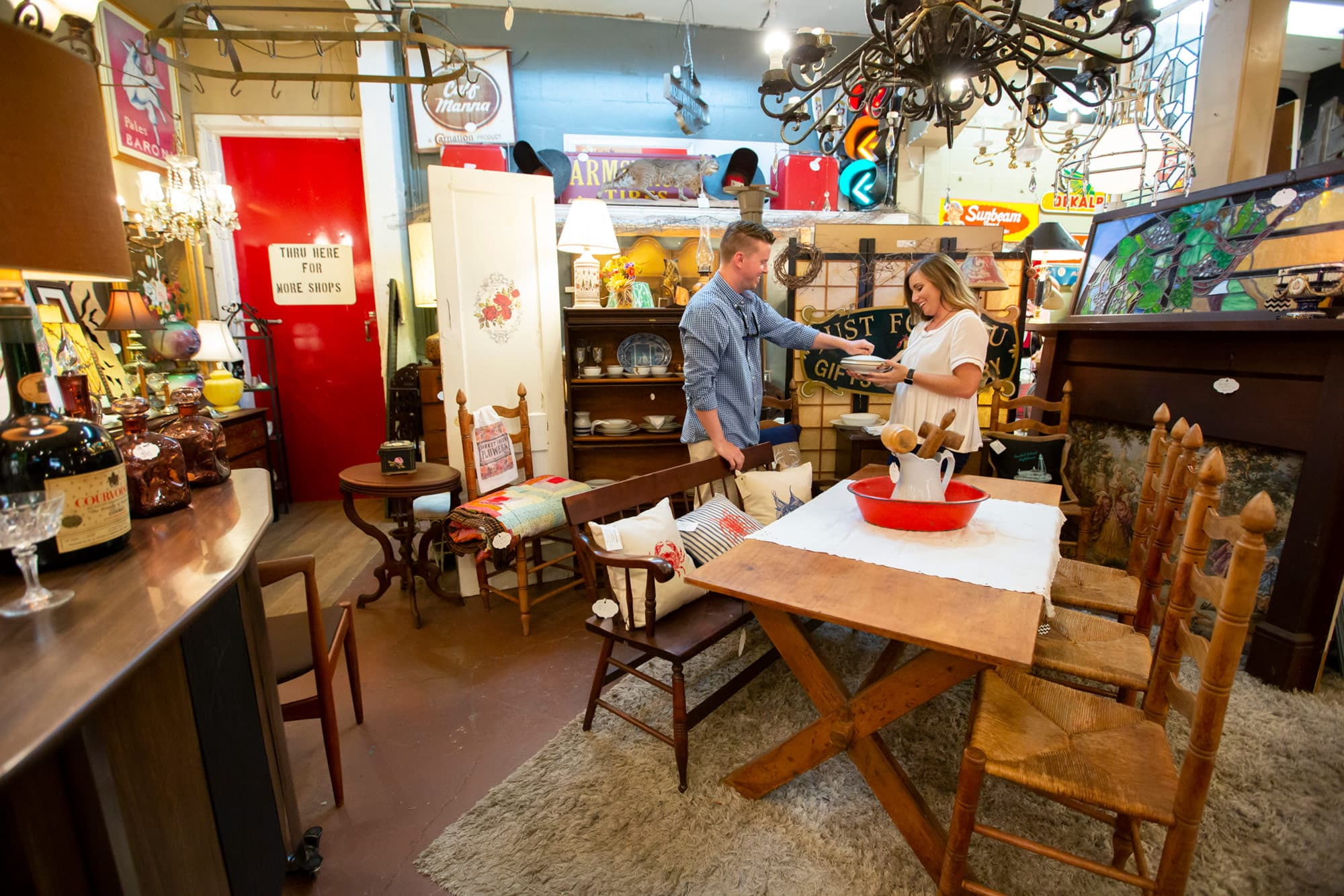 Couple looking at stoneware inside Dixieland Relics in Lakeland, FL. Home decor and antique furniture on display throughout room.