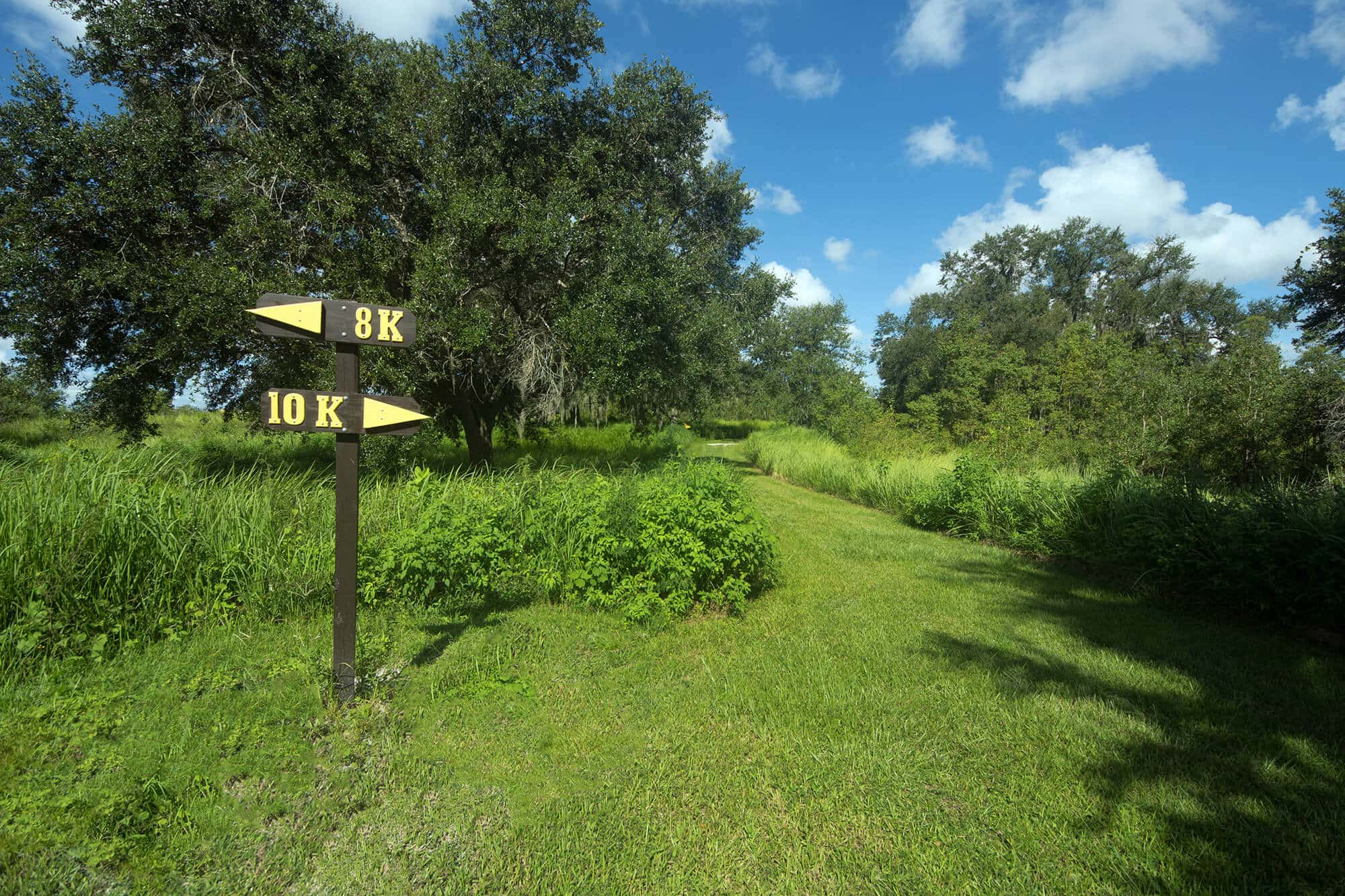 8K and 10K trail markers and grassy running path at Holloway Park in Lakeland, FL