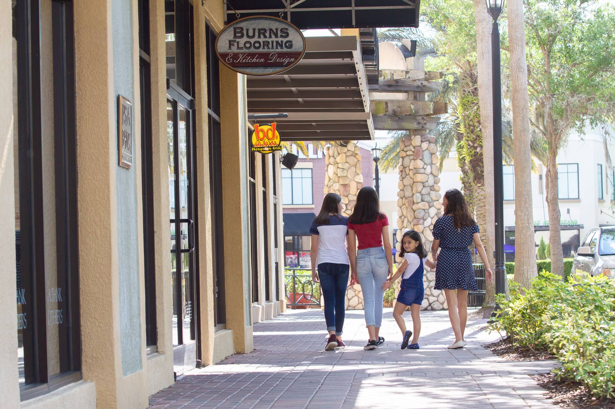 Mother and 3 daughters walking along sidewalk, in front of stores and restaurants at Lakeside Village in Lakeland.