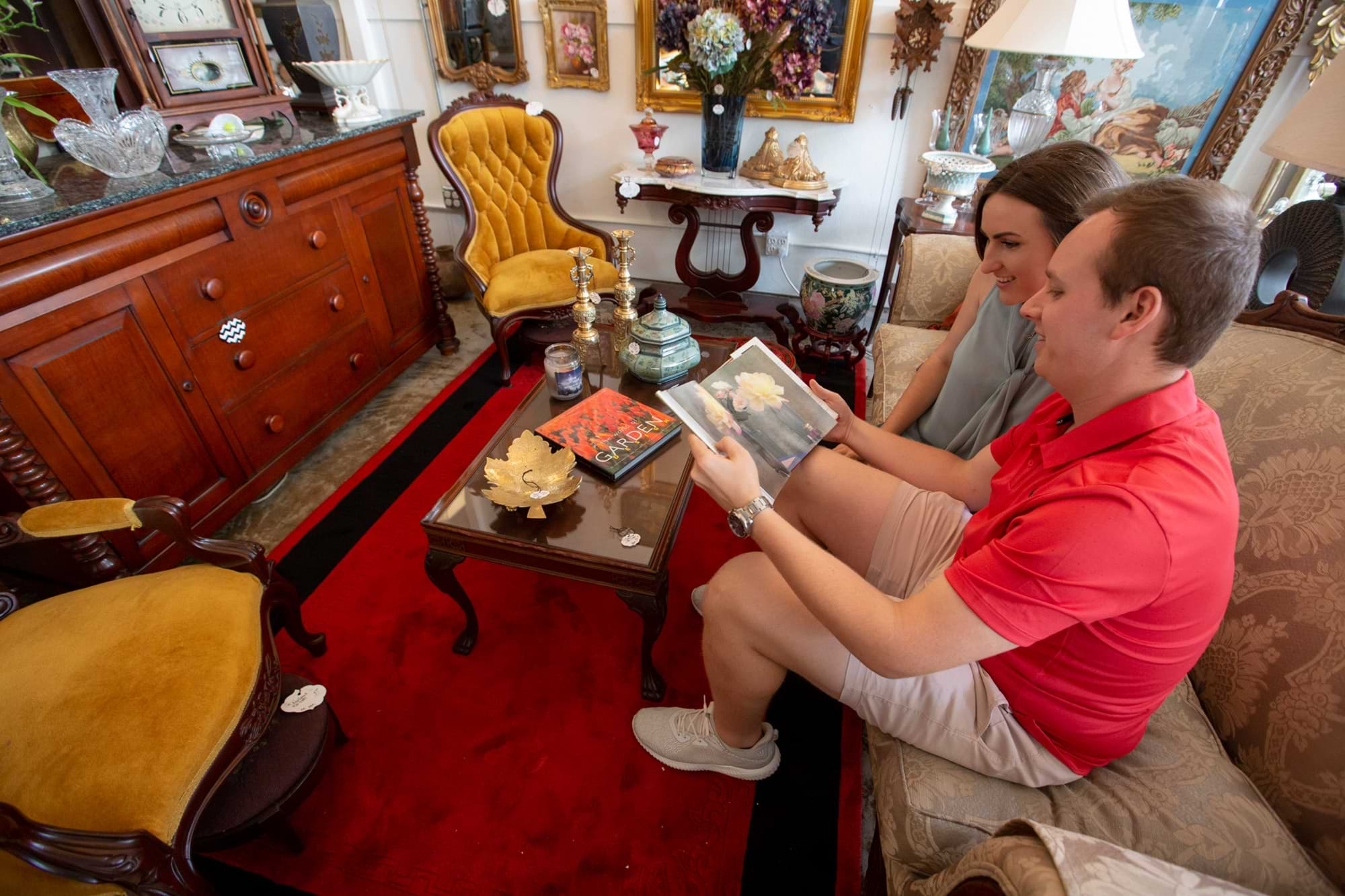 Couple looking at coffee table book while sitting on antique couch at Low Country Vintage in Lakeland, FL