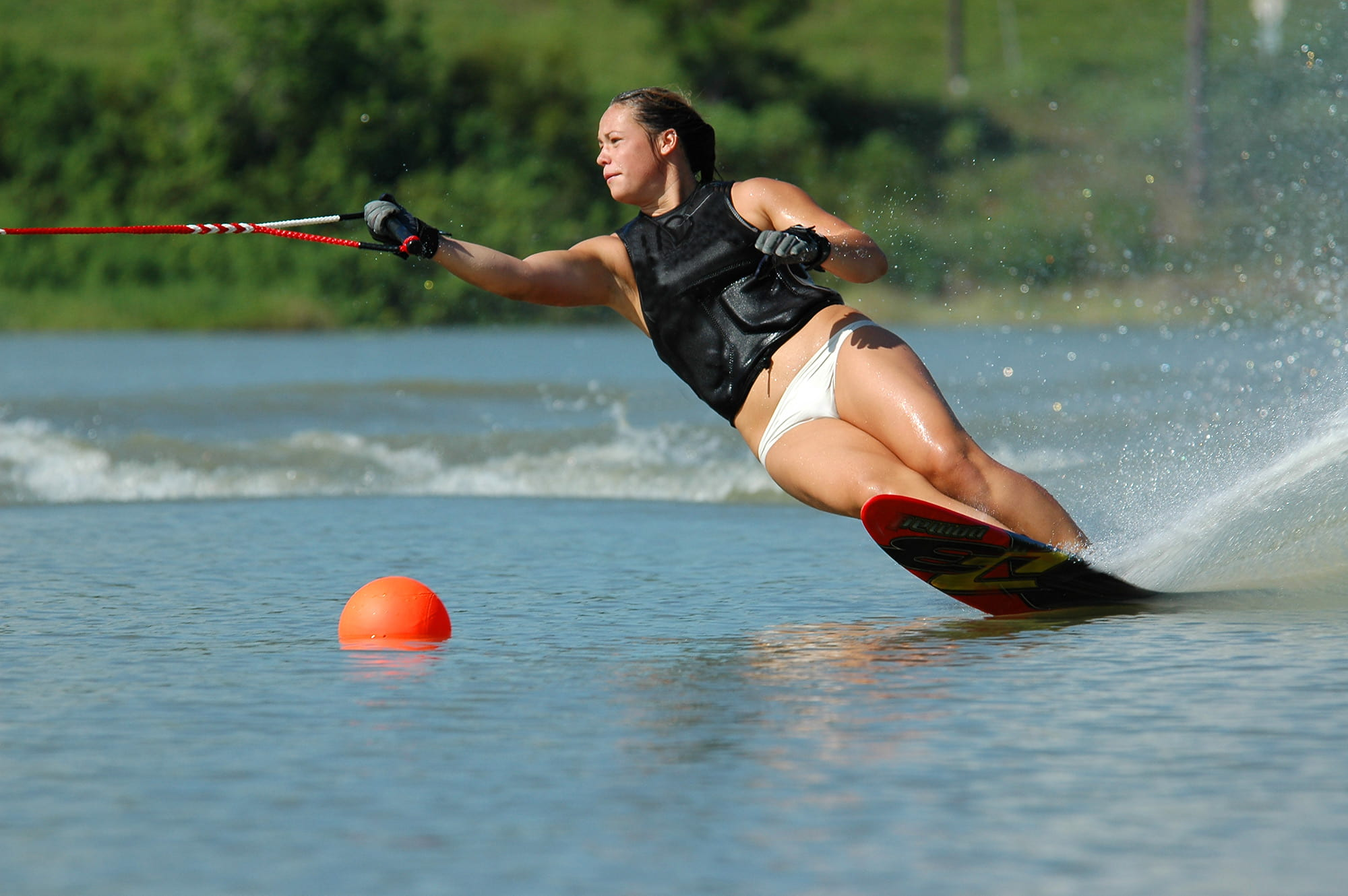 female slalom water skiing around buoy on lake, round a