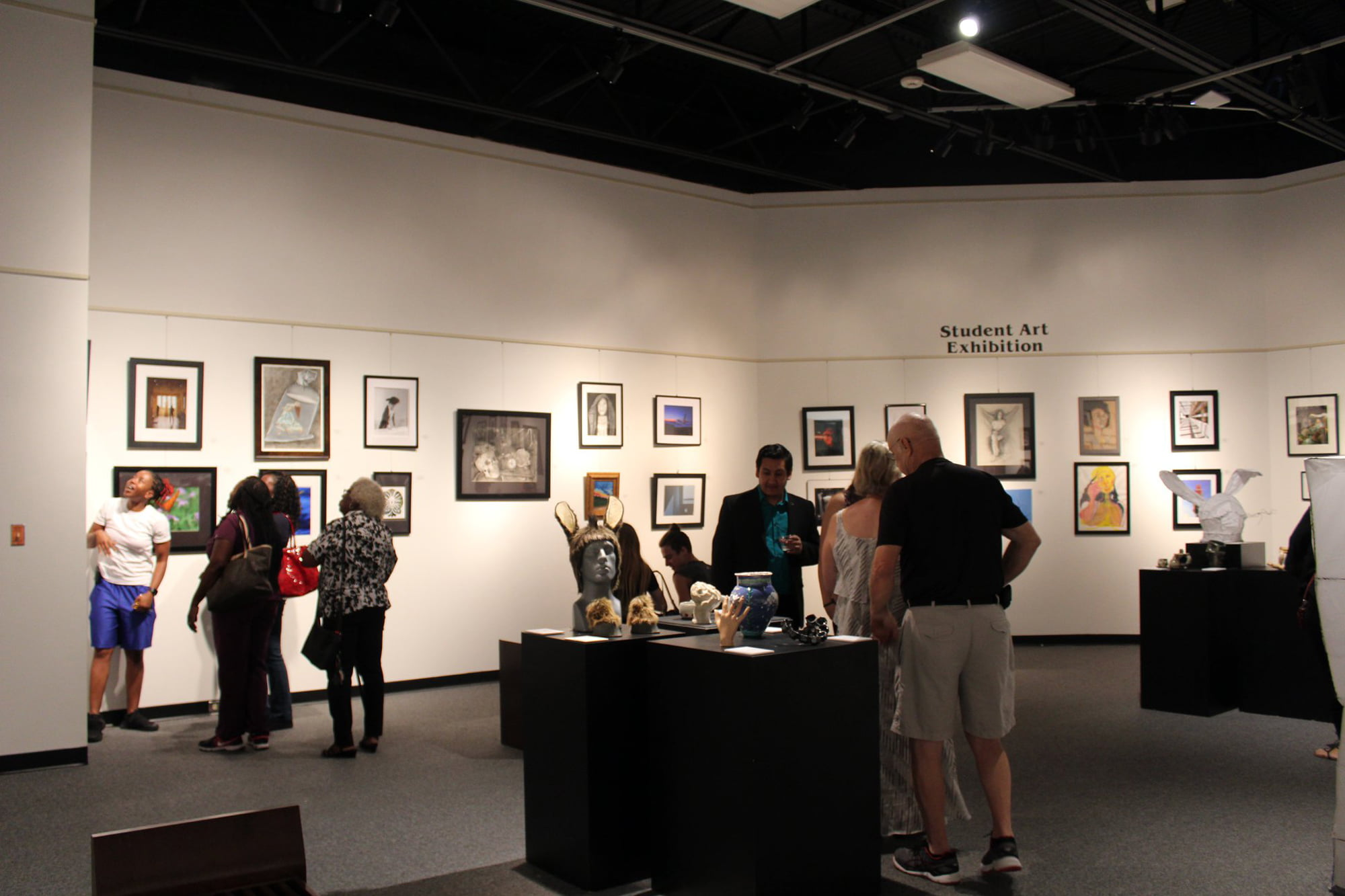 Visitors looking at art during Student Art Exhibition at Polk State College Lakeland Art Gallery.