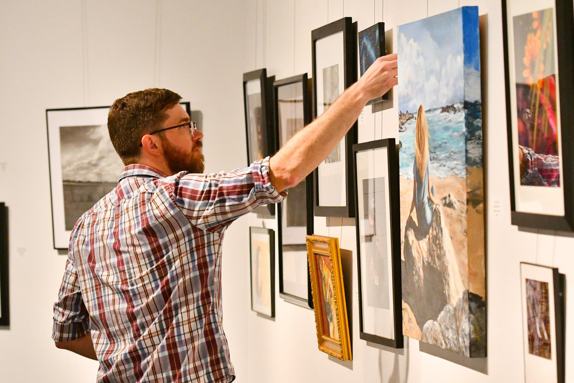 Person adjusting hanging art on display at Polk State College Winter Haven Art Gallery.