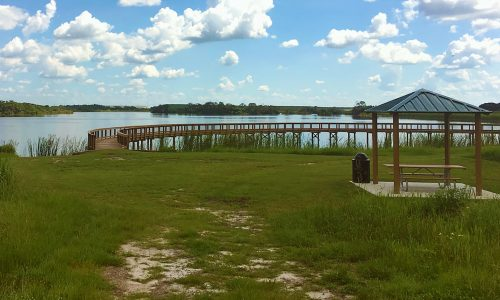 Grass and sand covered trail leading to covered pavilion with seating. Past the pavilion is entrance to wooden boardwalk expanding over a lake at Se7en Wetlands Park in Mulberry, FL