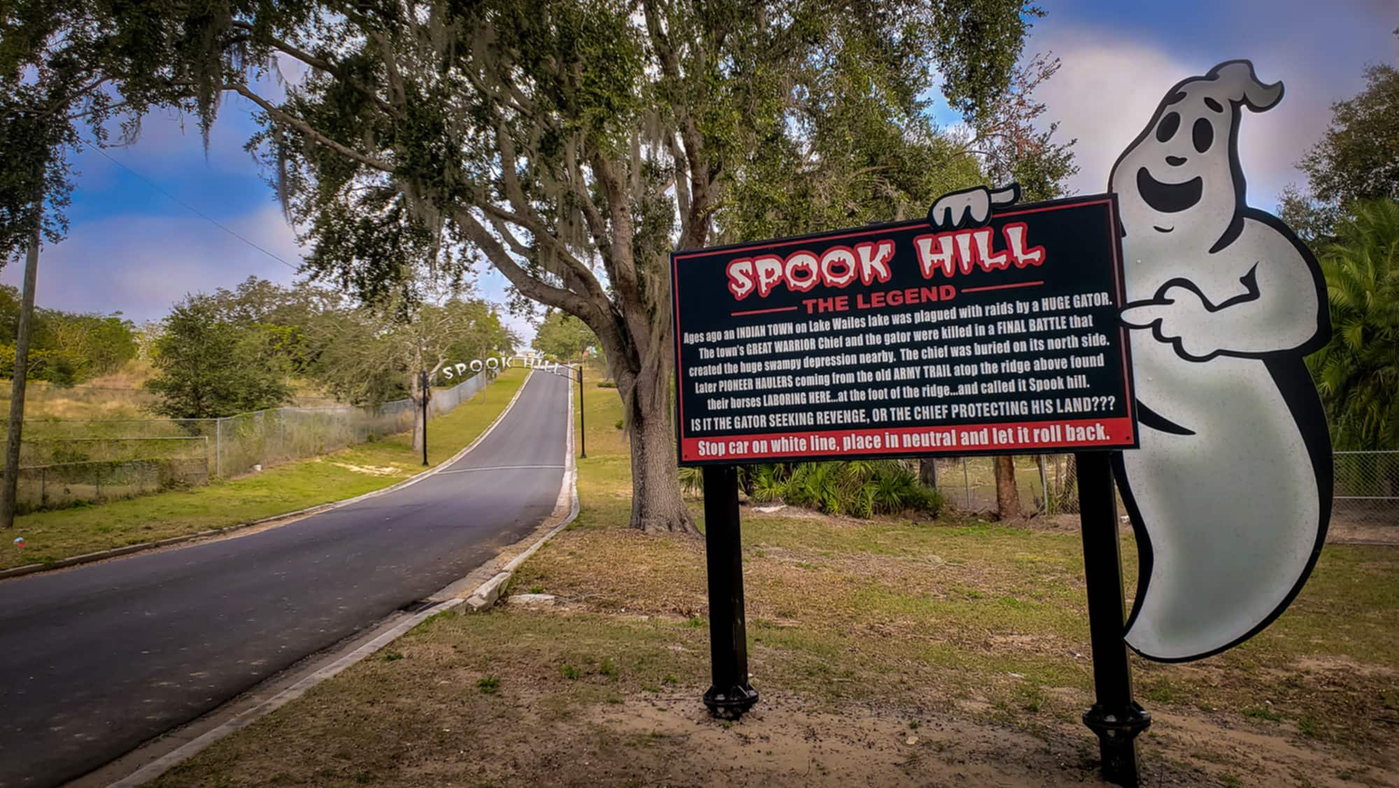 Road and sign explaining history of Spook Hill in Lake Wales, FL