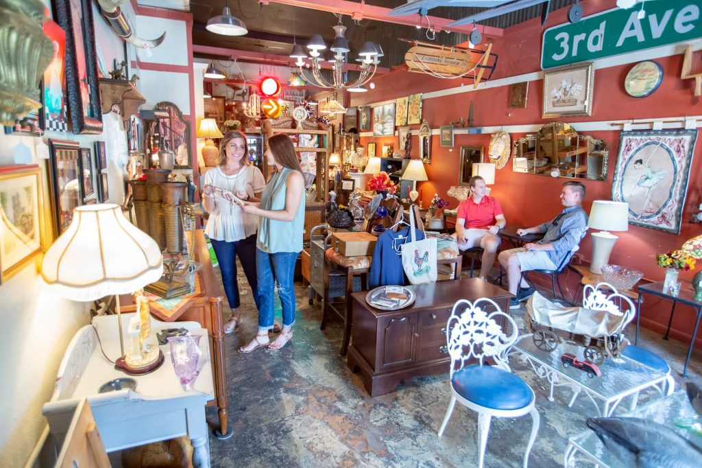 2 people shopping inside The Shop Across the Street in Lakeland, FL. Home decor and antique furniture on display.