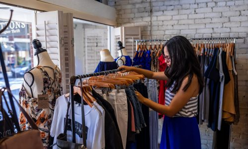 woman looking through clothes at Top Buttons Boutique and Designer Thrift