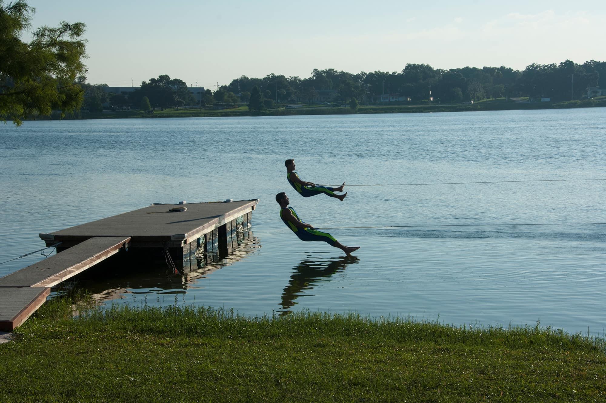 2 barefoot water skiers jumping from platform onto lake