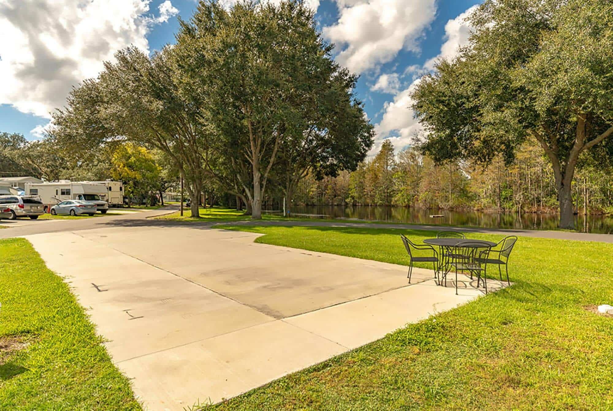 Kissimmee South RV Resort concrete back-in pad with picnic table and lake views.