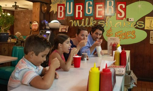 Family of 4 eating milkshakes at counter inside Andy's Drive-In Restaurant & Igloo in Winter Haven, FL