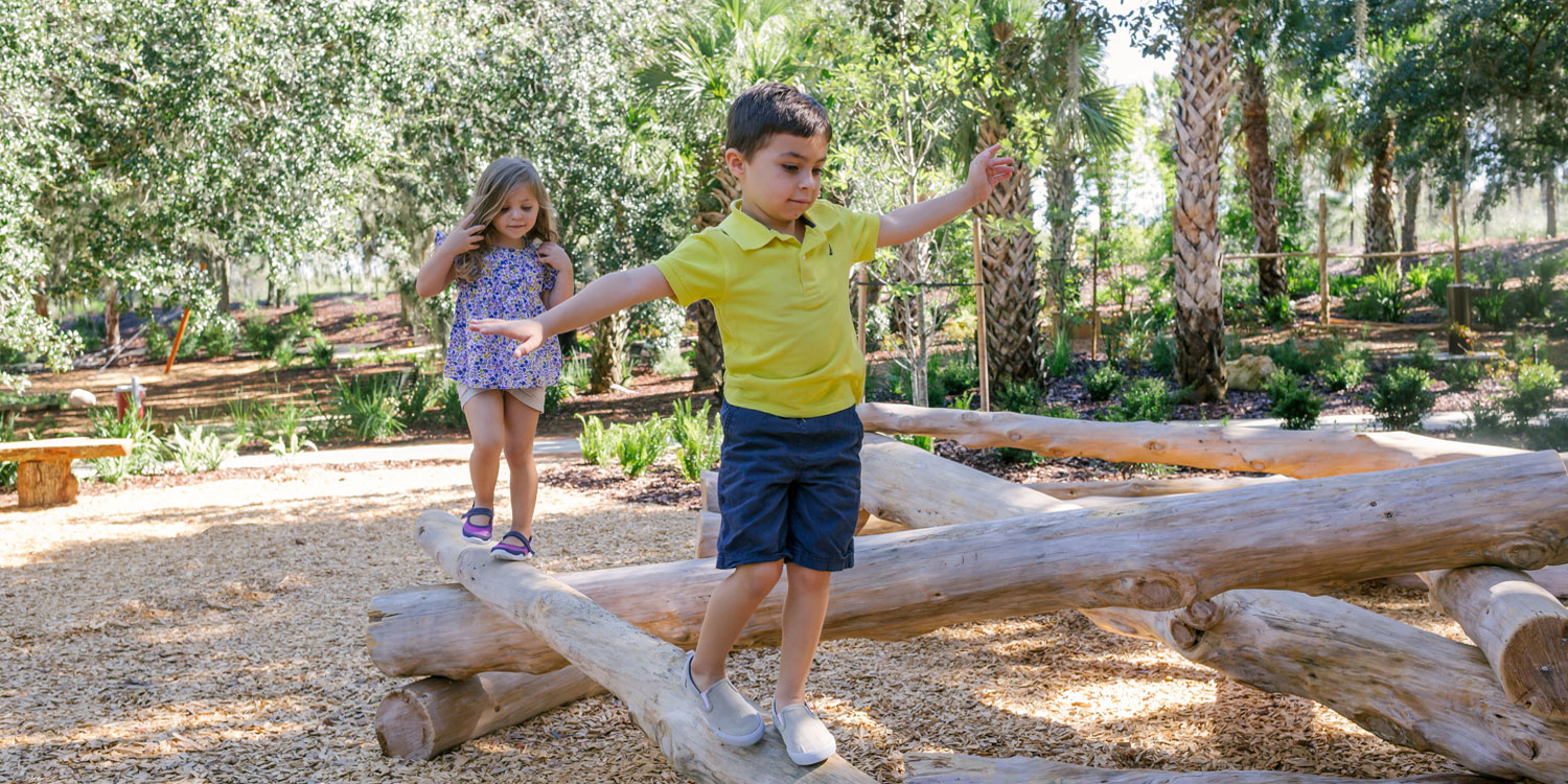 two kids walking on narrow logs at Hammock Hollow, a children's play area at Bok Tower Gardens in Lake Wales, FL