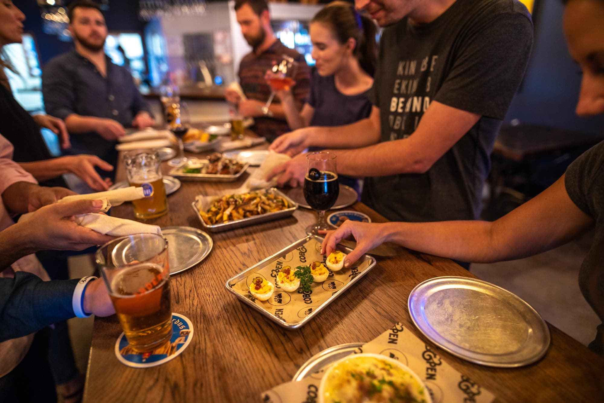 adults gathered around table at Cob & Pen in Lakeland, FL drinking beer and sharing small bite plates of deviled eggs, dip, french fries and wings