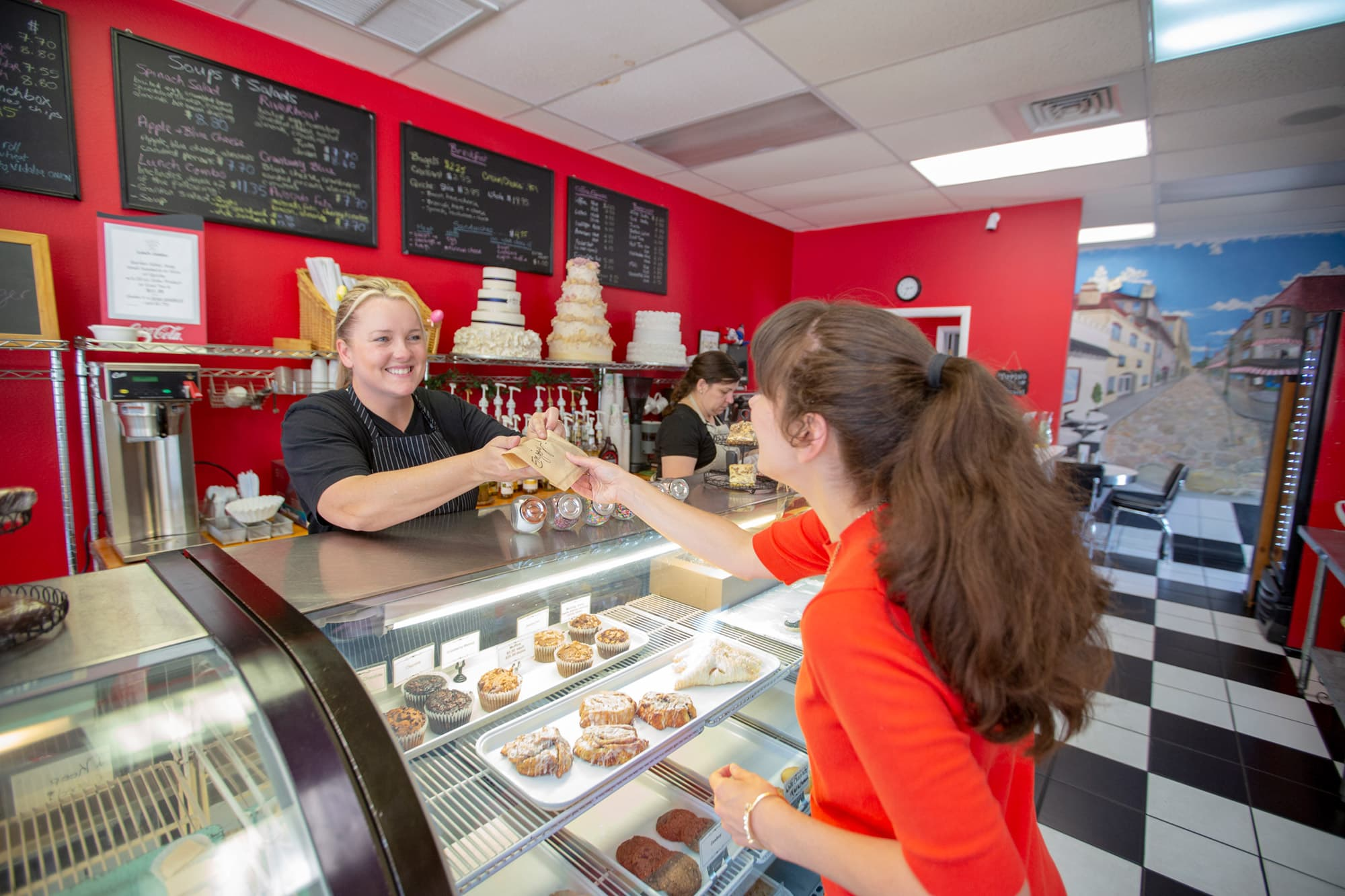 Woman handing purchased baked goods to customer over pastry filled bakery counter at Cookie Jar Bake Shop in Bartow, FL