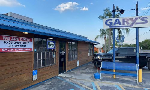 exterior of Gary's Oyster Bar. Entrance, sign and a parked truck