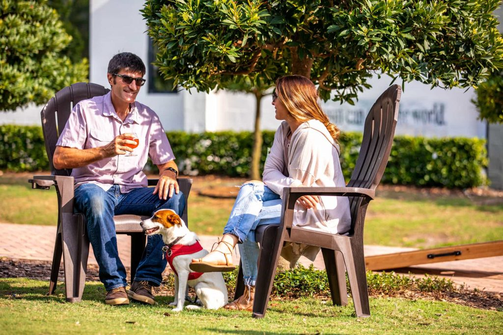 couple sitting outside on deck chairs with dog at Grove Roots Brewing Company in Winter Haven, FL