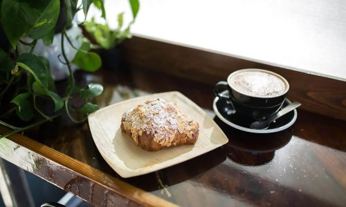 almond pastry on plate next to latte on wooden bar next to plant at N+1 Coffee