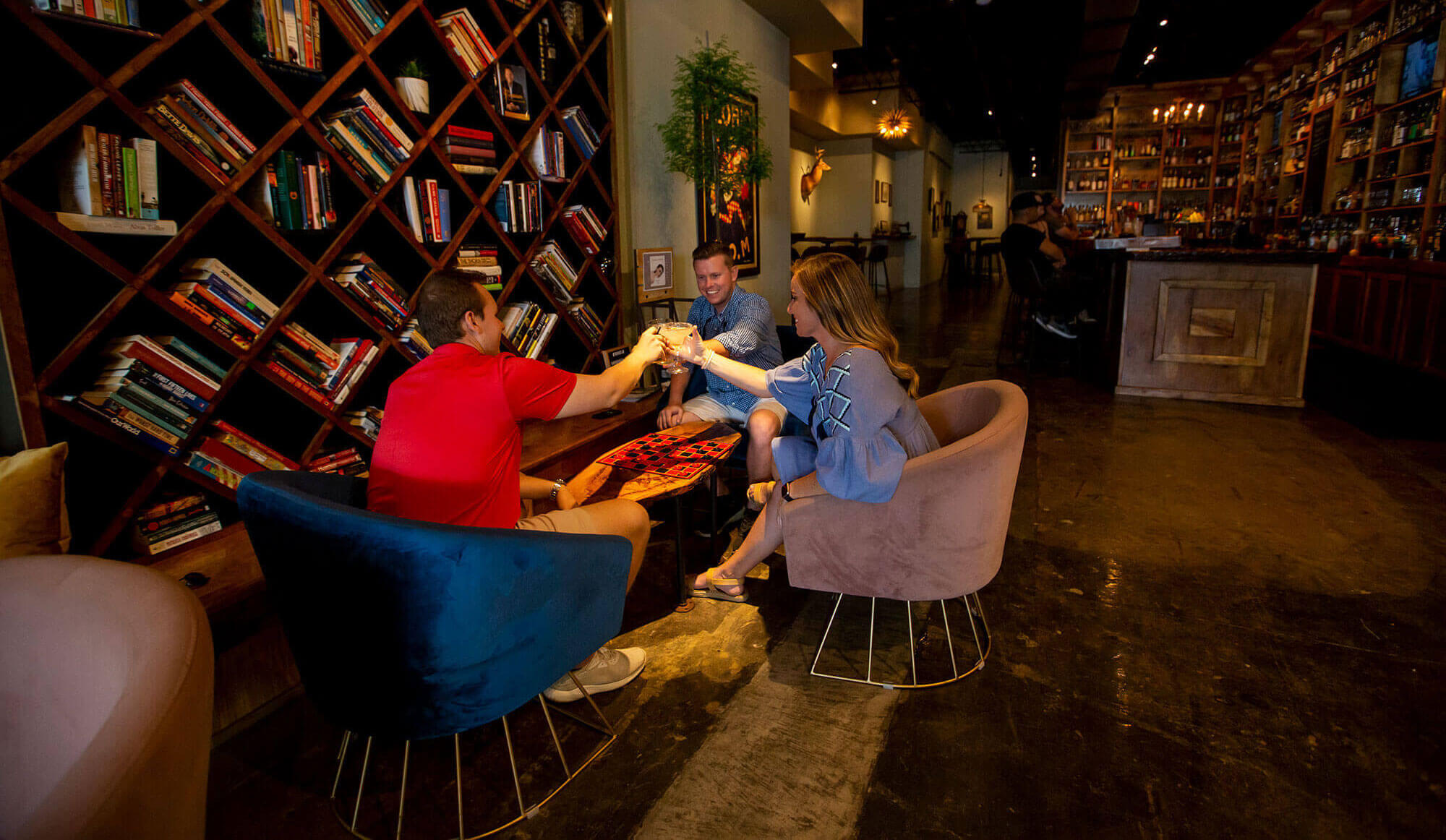 3 people sitting around a coffee table at Revival in Lakeland, FL. Shelved filled with books on side wall. Bar in background.