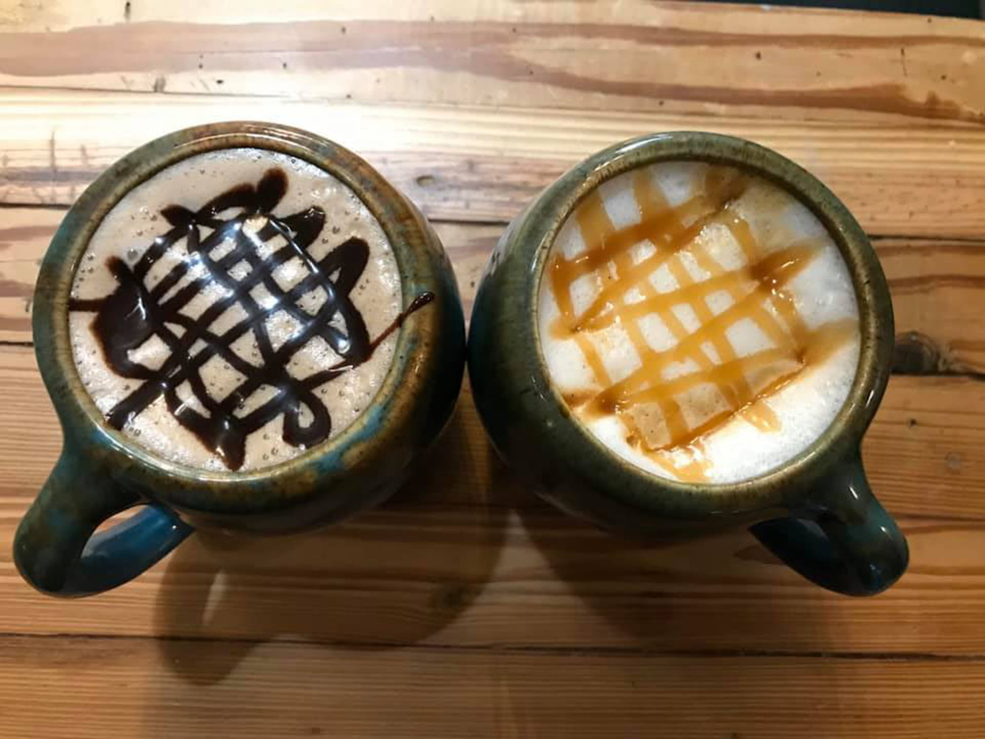 Two cups of coffee on wooden table. One with chocolate drizzle and one with caramel drizzle.