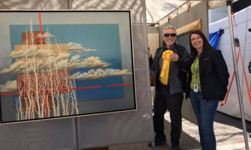 artist receiving ribbon next to painting at Bartow's Bloomin' Arts Festival