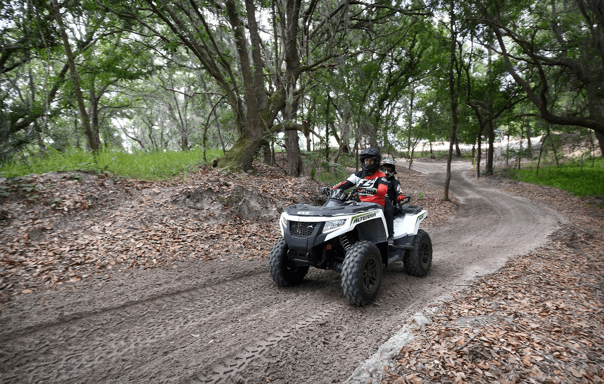 2 people on 4 wheeler riding on tree lined dirt trail at Bone Valley ATV Park in Mulberry, FL