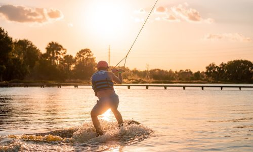 man wake boarding on lake at sunset at Elite Cable Park in Auburndale, FL