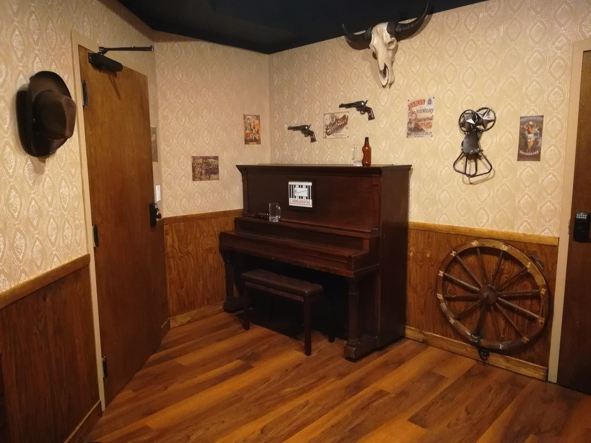 Arizona Shootout room with upright piano, wagon wheel and hanging skull at Escapology Escape Rooms in Lakeland, FL