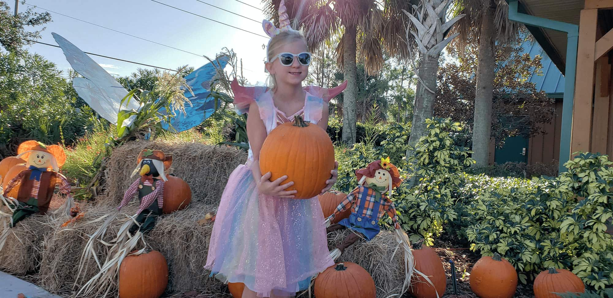 child holding pumpkin outside of Central Florida Visitor Information Center during Ghosts, Goblins, & Goodies