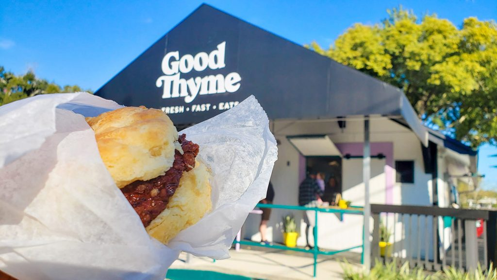 chicken biscuit being held up in front of Good Thyme LKLD. People ordering food in background.