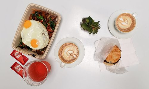 Food on white table. Vegan power bowl with two eggs, a chicken biscuit and Kombucha from Good Thyme LKLD. Two lattes from Concord Coffee.