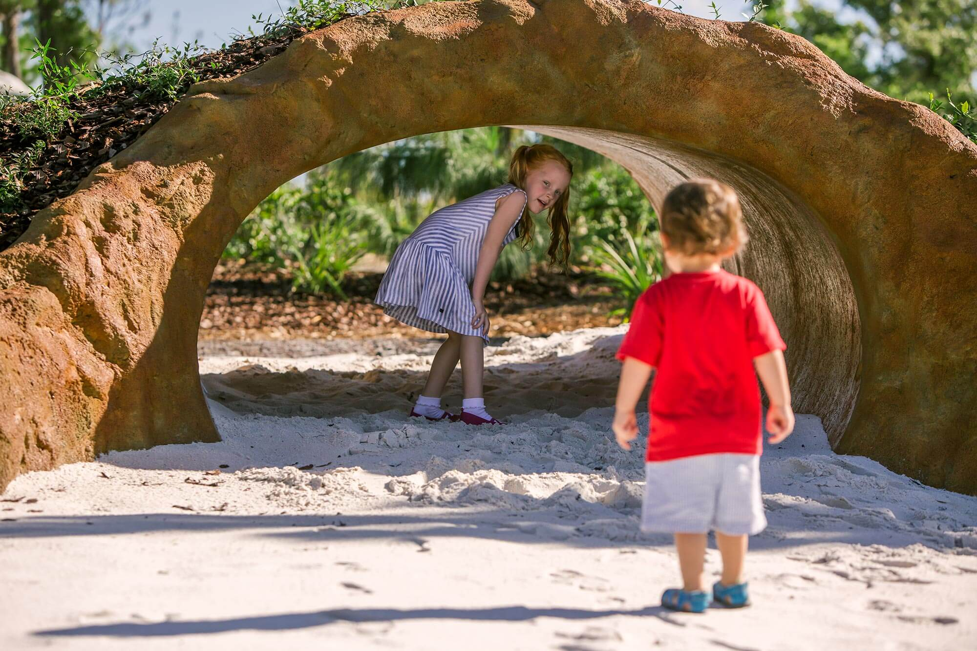 2 kids playing in Gopher Tortoise Burrow at Hammock Hollow in Bok Tower Gardens.