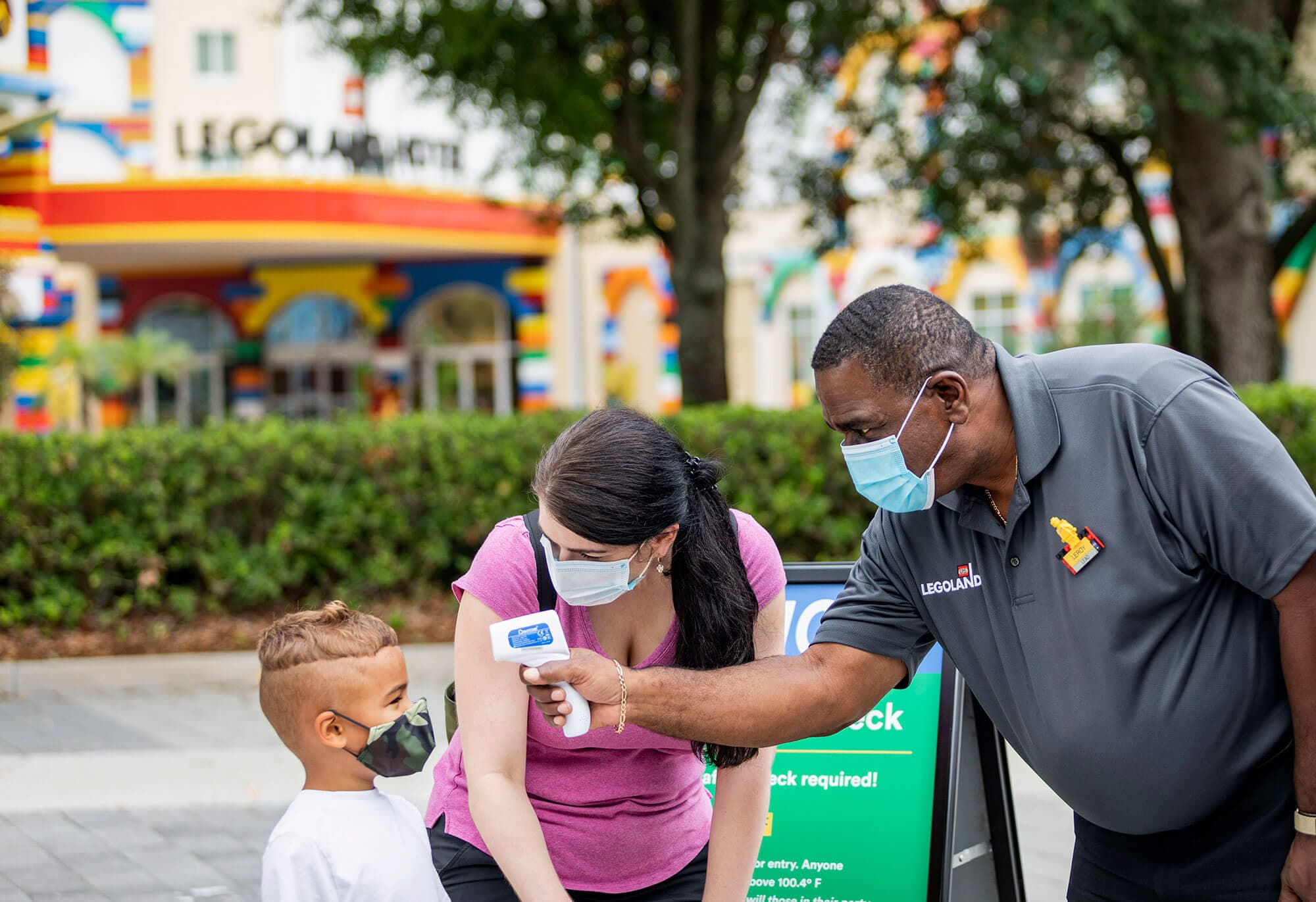 Staff member at LEGOLAND Florida Resort taking temp of young guest next to guest's mother. All three people are wearing masks. 3 cites in Polk County have mask requirements.