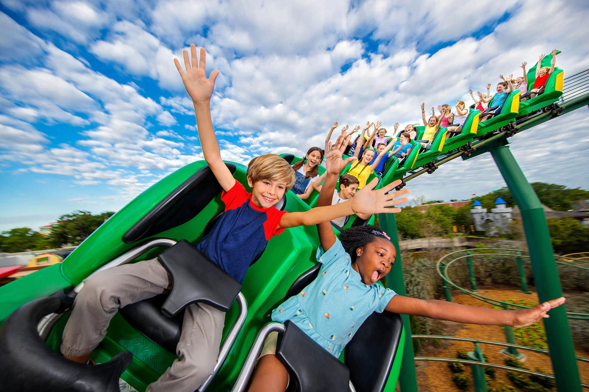 kids with hands up on Dragon Coaster Ride at LEGOLAND Florida Resort in Winter Haven, FL