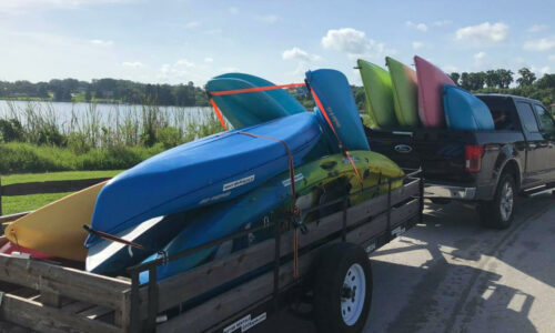 kayaks being transported on trailer and in back of a black truck with lake in background