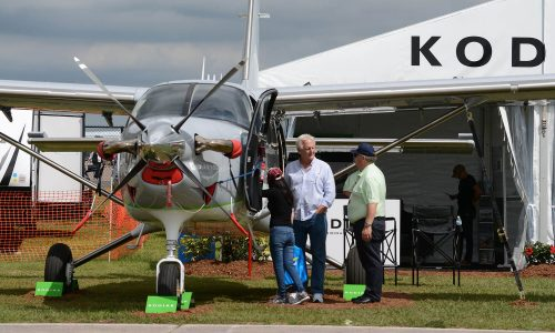 propeller airplane sale rep speaking with couple while looking at plane near vendor tent at SUN 'n FUN Aerospace Expo in Lakeland, FL