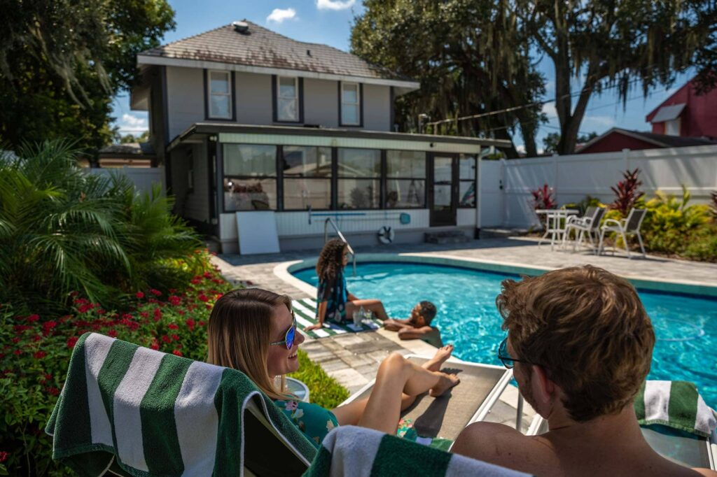 2 couples enjoying pool outside 2 story historic home Airbnb in downtown Lakeland