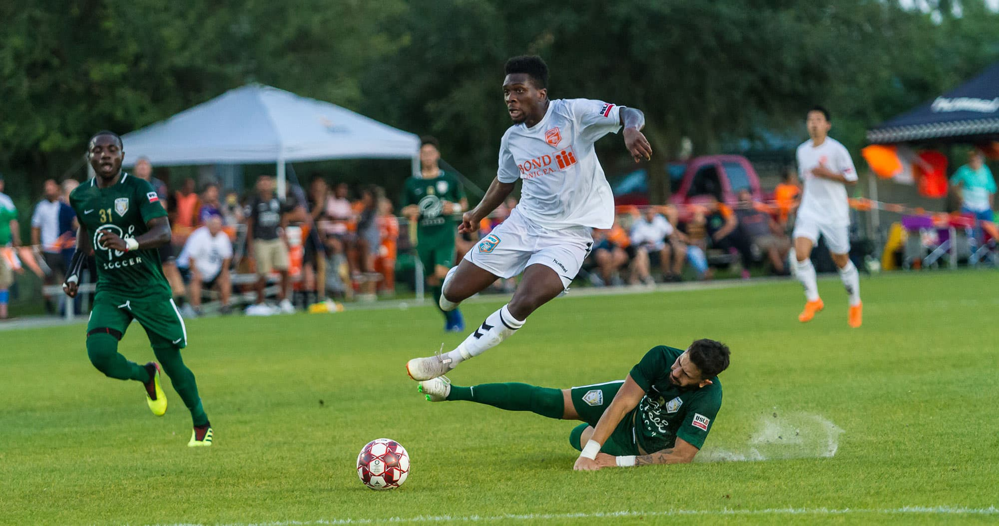 soccer player jumping over opponent to get to ball during Florida Tropics Soccer game at Lake Myrtle Sports Complex in Auburndale