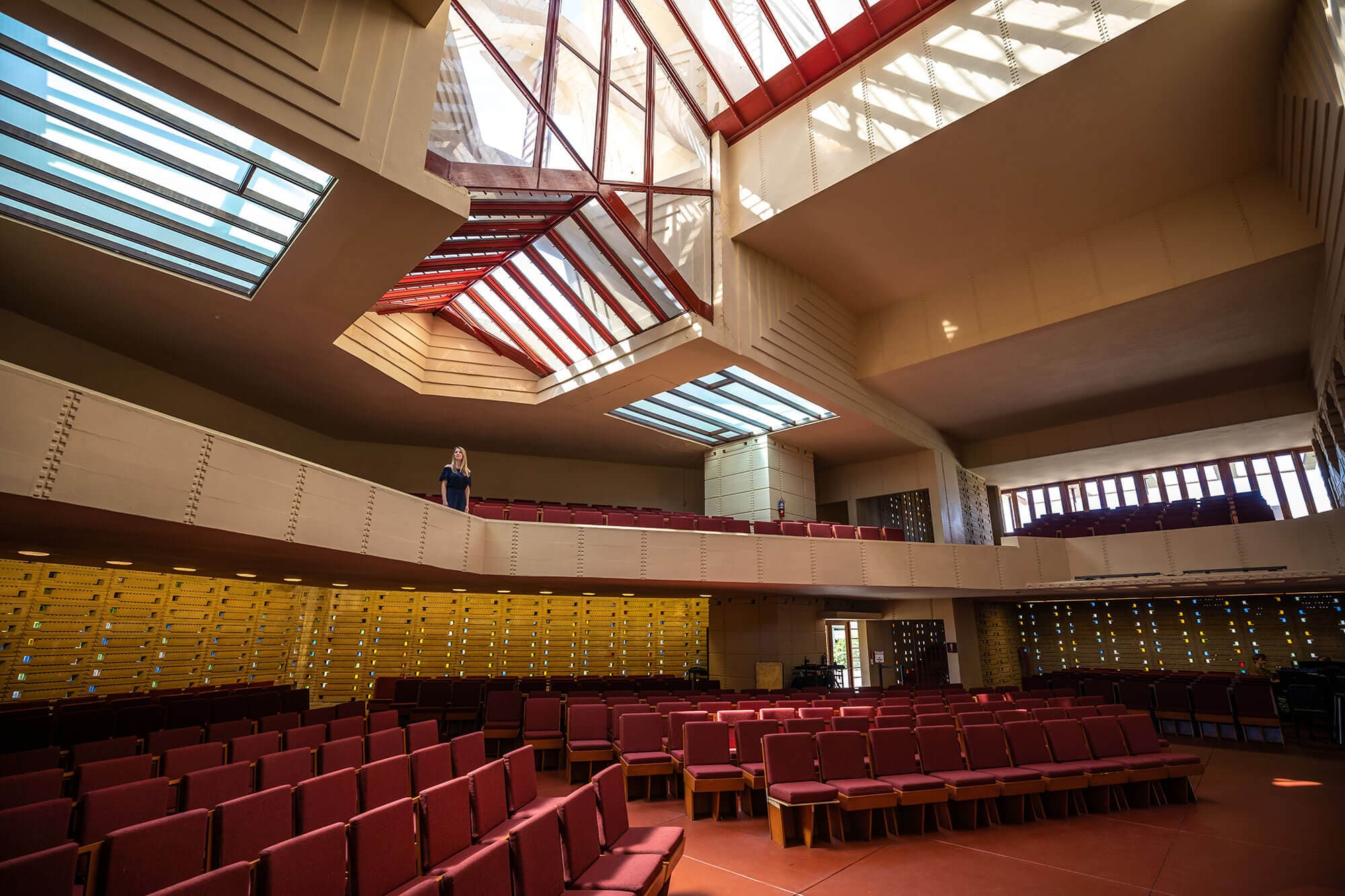Inside Frank Lloyd Wright's Annie Pfeiffer Chapel at Florida Southern College in Lakeland, FL. Woman standing in balcony seating area.