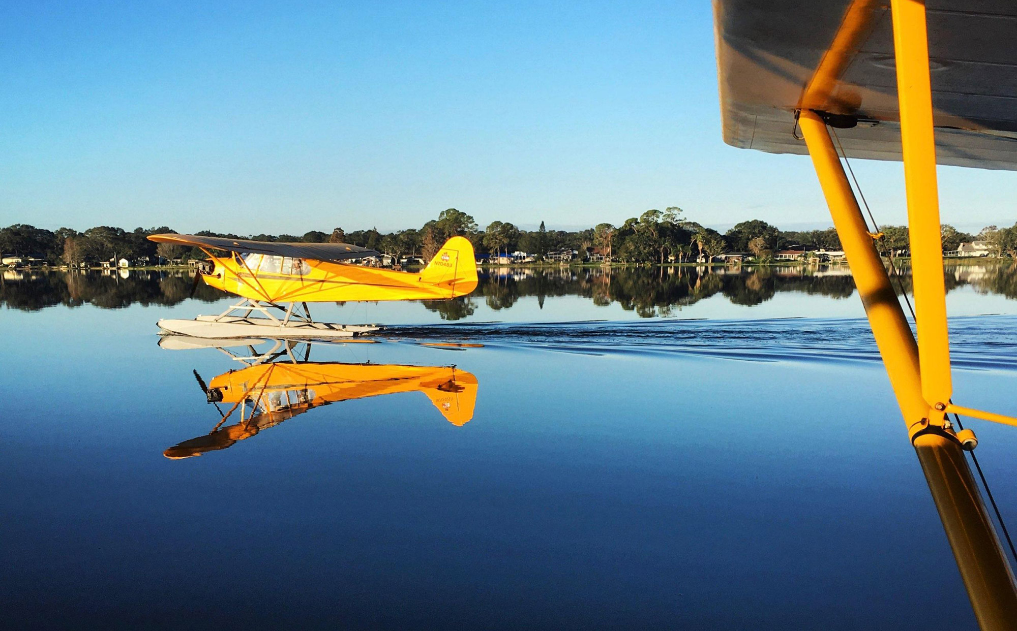 yellow seaplane taking off in lake at Jack Brown's Seaplane Base in Winter Haven, FL